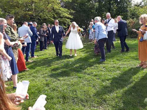 grass pathway with newly married couple