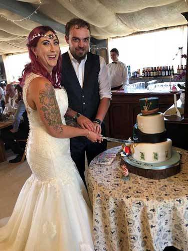 newly married couple cutting cake