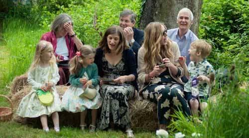 family sitting next to tree