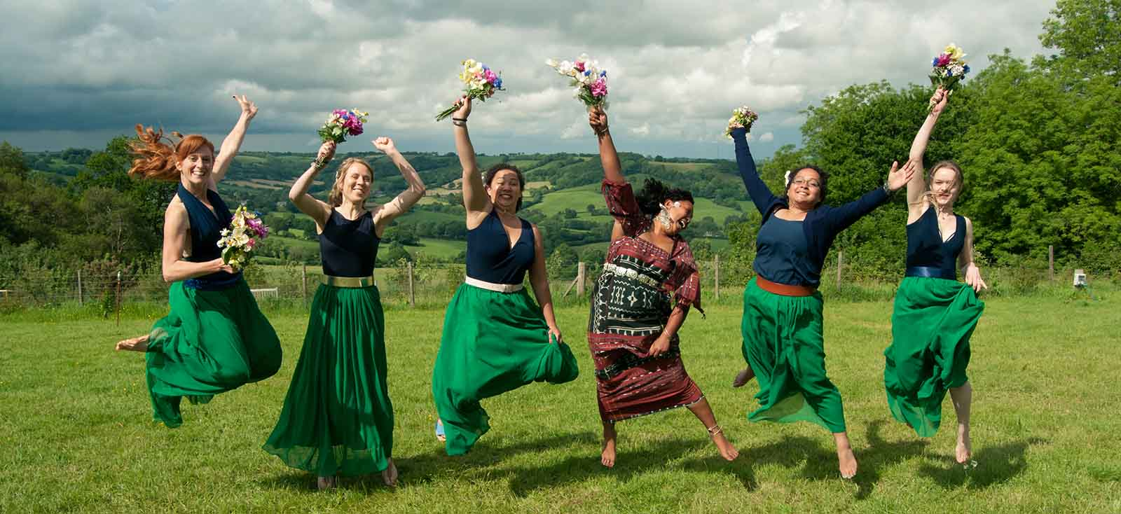 bridesmaids jumping in bovey down farm fields